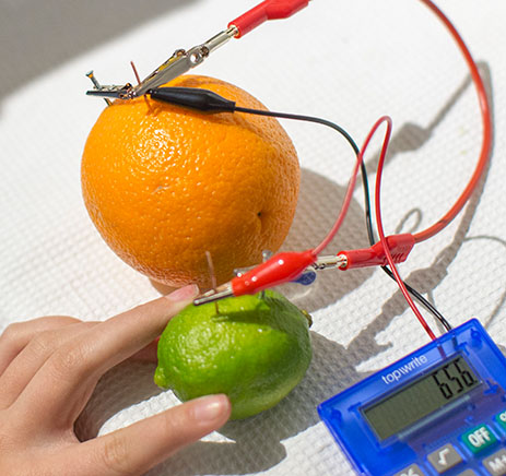 An orange and a lime connected with wires to a voltmeter.