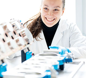 Woman in lab coat and blue gloves.